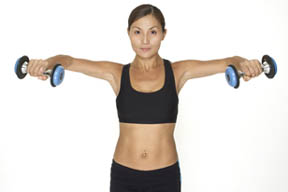 Model performs the contracting section of a standing dumbbell lateral raise